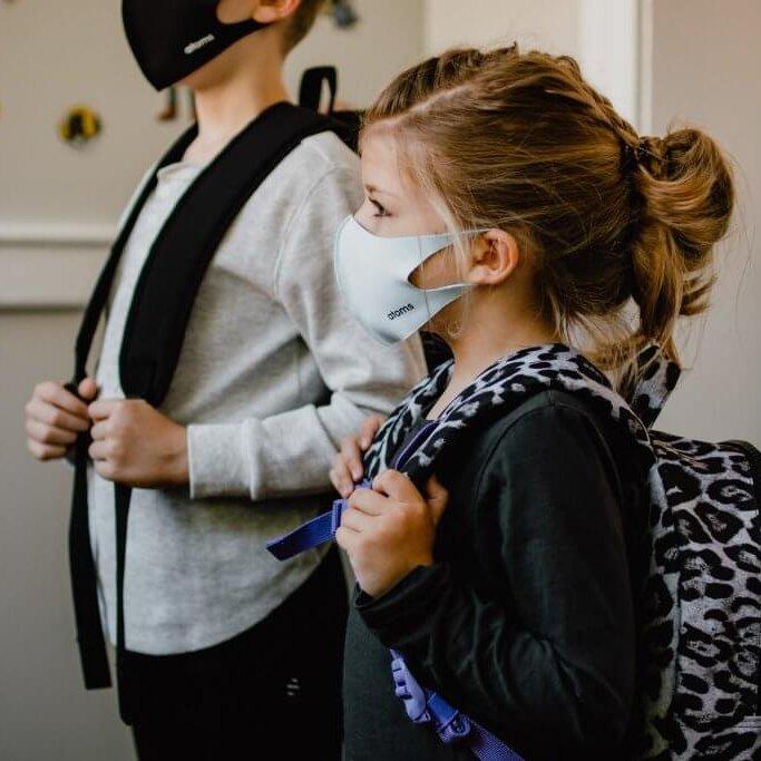 Children wearing backpacks and masks